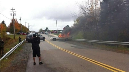 A police car is set on fire during the protest in Rexton, N.B. on Oct. 17, 2013.