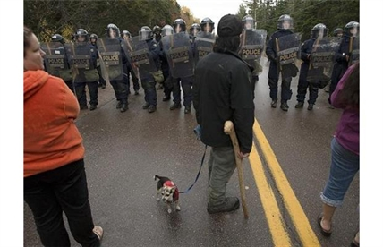 Protesters face a line of police officers in Rexton, N.B.