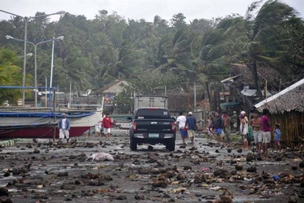 Debris litter the road by the coastal village in Legazpi city following a storm surge brought about by powerful Typhoon Haiyan.