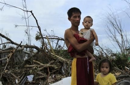 Roy Cagbian, 28, stands with his daughters, 7-month-old Shandev and 3-year-old Ashley in front of their home destroyed by Typhoon Haiyan in Tacloban, central Philippines, Monday, Nov. 11, 2013. Typhoon Haiyan, one of the strongest storms on record, slammed into six central Philippine islands on Friday leaving a wide swath of destruction and hundreds of people dead.
