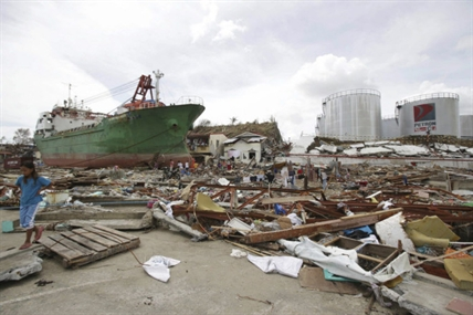 Survivors walk beside a ship that was washed ashore hitting makeshift houses near an oil depot in Tacloban city, Leyte province central Philippines on Monday, Nov. 11, 2013. Authorities said at least 2 million people in 41 provinces had been affected by Friday's typhoon Haiyan and at least 23,000 houses had been damaged or destroyed.