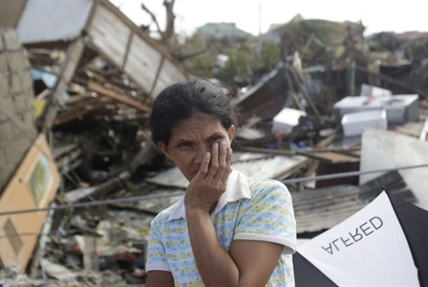 A survivor stands outside her damaged house at typhoon ravaged Tacloban city, Leyte province, central Philippines on Monday, Nov. 11, 2013. Authorities said at least 2 million people in 41 provinces had been affected by Friday's disaster and at least 23,000 houses had been damaged or destroyed.