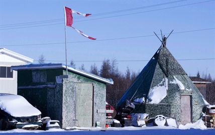 The remains of a Canadian flag can be seen flying over a building in Attawapiskat, Ont., on November 29, 2011.