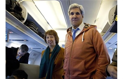 U.S. Secretary of State John Kerry, right, and EU foreign policy chief Catherine Ashton, left, visit the media seating area of Kerry's aircraft as it sits on the tarmac at Geneva International airport before leaving for London, Sunday, Nov. 24, 2013, in Geneva, Switzerland. A deal has been reached between six world powers and Iran that calls on Tehran to limit its nuclear activities in return for sanctions relief, the French and Iranian foreign ministers said early Sunday.