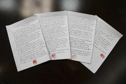 In this Nov. 9, 2013 photo released by the Korean Central News Agency (KCNA) and distributed Nov. 30, 2013 by the Korea News Service, hand written statements with red thumb prints, which North Korean authorities say is an apology written and read by 85-year-old U.S. citizen Merrill Newman, lie on a table in North Korea. Newman, an avid traveler and retired finance executive, was taken off a plane Oct. 26 by North Korean authorities while preparing to leave the country after a 10-day tour.