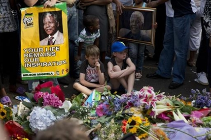 Children look at tributes outside the home of former president Nelson Mandela in Johannesburg, South Africa, Saturday, Dec. 7, 2013.