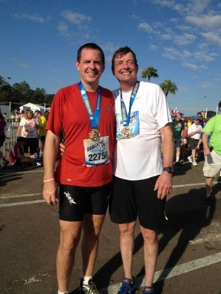 In this Jan. 12, 2013 photo provided by the family, Doug Olson, right, and his son, Jon, stand together after running a half-marathon in Orlando, Fla. As of December 2013, Doug Olson, 67, a scientist for a medical device maker, shows no sign of cancer since gene therapy in September 2010 for chronic lymphocytic leukemia he had had since 1996.