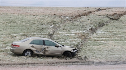A car that slid off the road sits on the side of the highway near Waxahachie, Texas on Saturday, Dec. 7, 2013.