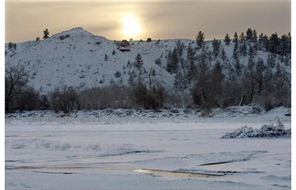 The sun rises over the hills south of the Yellowstone River in Billings, Mont. as the temperatures hover around 20 degrees below zero on Saturday, Dec. 7, 2013.