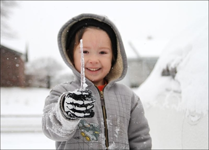 Jared Shepard, 5, plays in the snow in his front yard after several inches of snow and ice blanketed the area Friday, Dec. 7, 2013 in Van Buren, Ark.