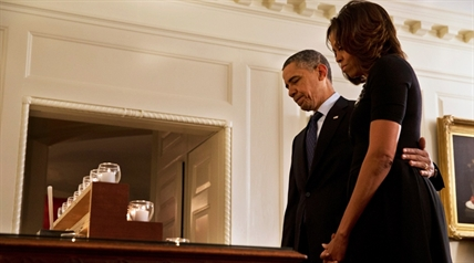 President Barack Obama and first lady Michelle Obama take a moment of silence in honor of the Newtown shooting victims on the one year anniversary of the tragedy, in the Map Room of the White House in Washington, Saturday, Dec. 14, 2013.