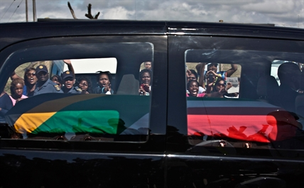 South African mourners wave and cheer as the hearse transporting the body of Former President Nelson Mandela passes through the town of Mthatha on its way to Qunu, South Africa, Saturday, Dec. 14, 2013.