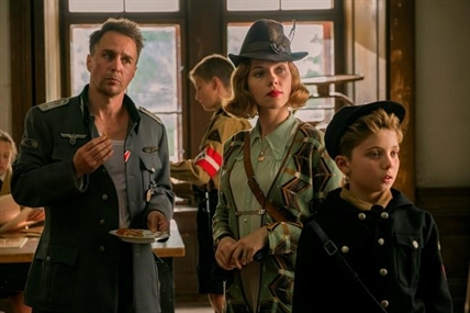 "This image released by Fox Searchlight Pictures shows, from left, Sam Rockwell, Scarlett Johansson and Roman Griffin Davis in a scene from the WWII satirical film ""Jojo Rabbit."""