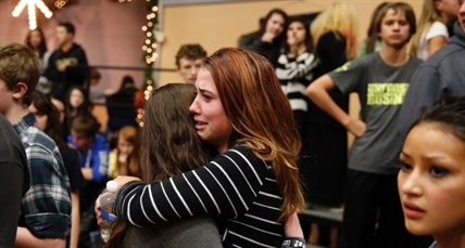 Freshman Allie Zadrow, center right, hugs classmate Liz Reinhardt at a church after a shooting at nearby Arapahoe High School in Centennial, Colo., on Friday, Dec. 13, 2013.