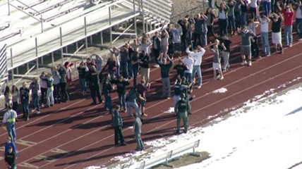 In this still image taken from video provided by Fox 31 Denver, students gather just outside of Arapahoe High School as police respond to reports of a shooting at Arapahoe High School in Centennial, Colo. Friday, Dec. 13, 2013.