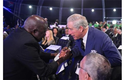Britain's Prince Charles, right, is greeted by another mourner as he arrives for the funeral service for former South African president Nelson Mandela in Qunu, South Africa, Sunday, December 15, 2013.
