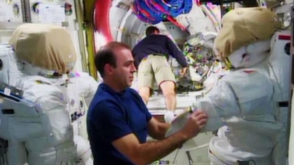 Expedition 38 crew member Rick Mastracchio, left, checks out the spacesuit that he will wear during a spacewalk with crew member Mike Hopkins, in the Quest airlock in the International Space Station in this undated image taken from video from NASA TV. Mastracchio and fellow astronaut Mike Hopkins will conduct a series of spacewalks beginning Saturday, Dec. 21, 2013 to replace an ammonia pump that is part of the station's coolant system. This will be Hopkins' first spacewalk, while Mastracchio has had six previous ones.