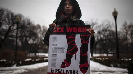 A woman (requested to withhold her name) holds a sign during a rally at Allan Gardens park to support Toronto sex workers and their rights in Toronto, Friday December 20, 2013.