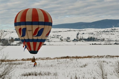 A hot air balloon lands beside Swan Lake.