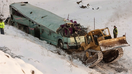 A piece of heavy equipment strains to move a bus which plummeted 200 feet down an embankment in rural Eastern Oregon the day before, on Monday, Dec. 31, 2012.