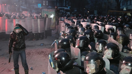 A protester stands in front of riot police in central Kiev, Ukraine, Sunday, Jan. 19, 2014.