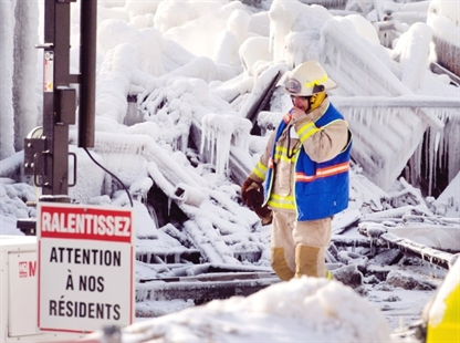 An emergency worker walks past a sign that reads