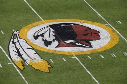 "FILE - In this Aug. 7, 2014 file photo, the Washington Redskins NFL football team logo is seen on the field before an NFL football preseason game against the New England Patriots in Landover, Md. The recent national conversation about racism has renewed calls for the Washington Redskins to change their name. D.C. mayor Muriel Bowser called the name an ""obstacle"" to the team building its stadium and headquarters in the District, but owner Dan Snyder over the years has shown no indications he'd consider it."