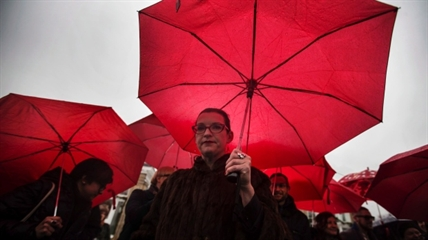 People hold red umbrellas, that are used as a symbol for sex workers rights, at a rally at Allan Gardens park to support Toronto sex workers and their rights in Toronto, Friday December 20, 2013.
