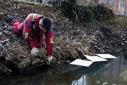 Investigators check a culvert pipe as a potential source for the spill.