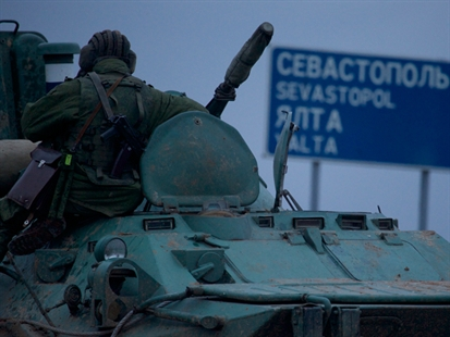 A soldier rests atop a Russian armoured personnel carrier near the town of Bakhchisarai, Ukraine on Friday, Feb. 28, 2014. The border between Russia and Ukraine is all but open, labour flows freely, goods are exchanged without customs and three million Ukrainians work in Russia now.