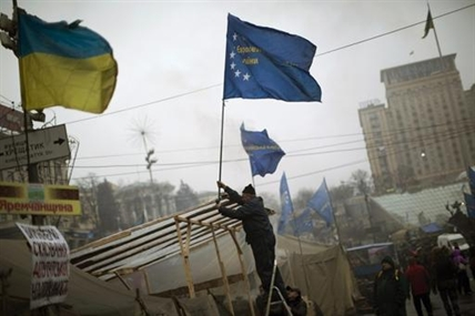 An anti-Yanukovych protester sets an European Union flag on top of a tent in Kiev's Independence Square, the epicenter of the country's current unrest, Ukraine, Sunday, March 2, 2014.