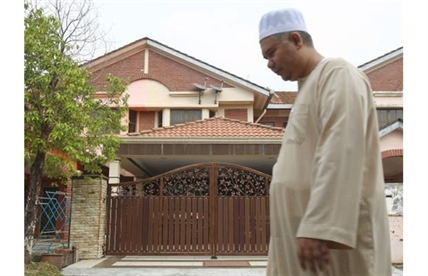 A Muslim man walks past the missing Malaysia Airlines co-pilot Fariq Abdul Hamid's house after a prayer in Shah Alam, outside Kuala Lumpur, Malaysia, Saturday, March 15, 2014.