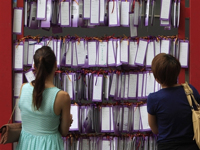 People read message cards tied up for passengers aboard a missing Malaysia Airlines plane, outside a shopping mall in Kuala Lumpur, Malaysia, Friday, March 14, 2014.