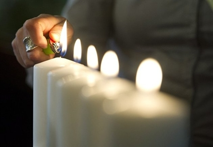 A candle is lit at a memorial event held at the University of Calgary on Thursday, April 17, 2014