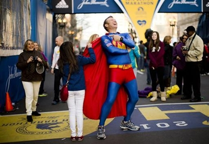 "Trent Morrow of Sydney, Australia, also know as ""Marathon Man"" laughs as Andrea Olivo of Venezuela tugs on his cape as she has her photo made ahead of Monday's 118th Boston Marathon, Sunday, April 20, 2014, in Boston. Morrow says Monday's marathon will be his 200th run since Jan. 1, 2013."