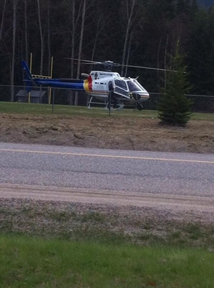 A RCMP helicopter lands in the field at Clearwater Secondary School on Monday, April 21, 2014.