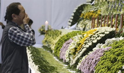 A mourner weeps as he pays tribute to the victims of the sunken ferry Sewol in the water off the southern coast at a gymnasium, in Ansan, South Korea, Wednesday, April 23, 2014.