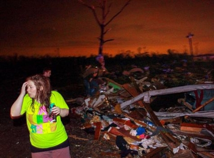 In this Sunday, April 27, 2014 photo, Lauren Watts searches for her dog in Mayflower, Ark., after a tornado struck the town. A tornado system ripped through several states in the central U.S. and left more than a dozen dead in a violent start to this year's storm season, officials said.