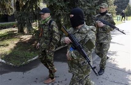 Vacheslav Ponomarev, left, the self-proclaimed mayor of Slovyansk, surrounded by bodyguards, walks in Slovyansk, eastern Ukraine, Saturday, May 3, 2014.