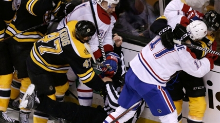 An official tumbles to the ice as Boston Bruins players fight with Montreal Canadiens players during the second period of Game 2 in the second-round of the Stanley Cup hockey playoff series in Boston, Saturday, May 3, 2014.