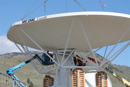 Engineers secure the dish to the tower.