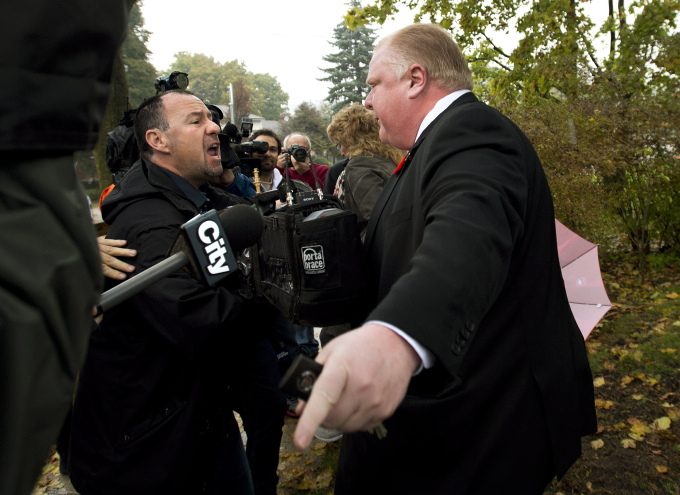 City of Toronto Mayor Rob Ford, right, reacts to the media to get off his  property as he leaves his home in Toronto on Thursday, Oct. 31, 2013.